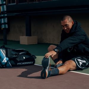 Stretching before Pickleball match beside ProKennex Tour Bag